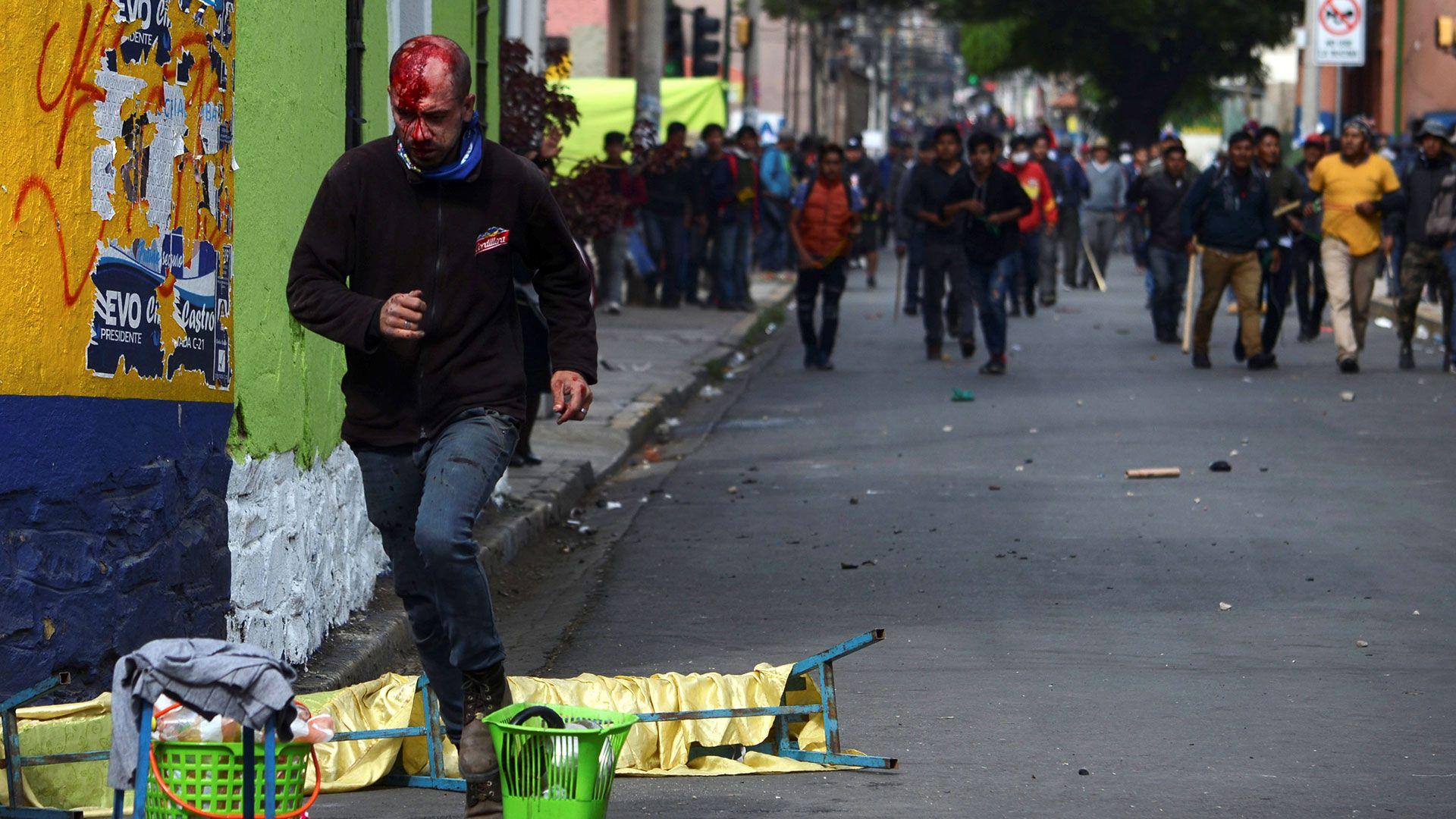 Una persona herida escapa de manifestantes violentos que salieron a las calles a acallar las protestas que denuncian fraude en las elecciones bolivianas.
