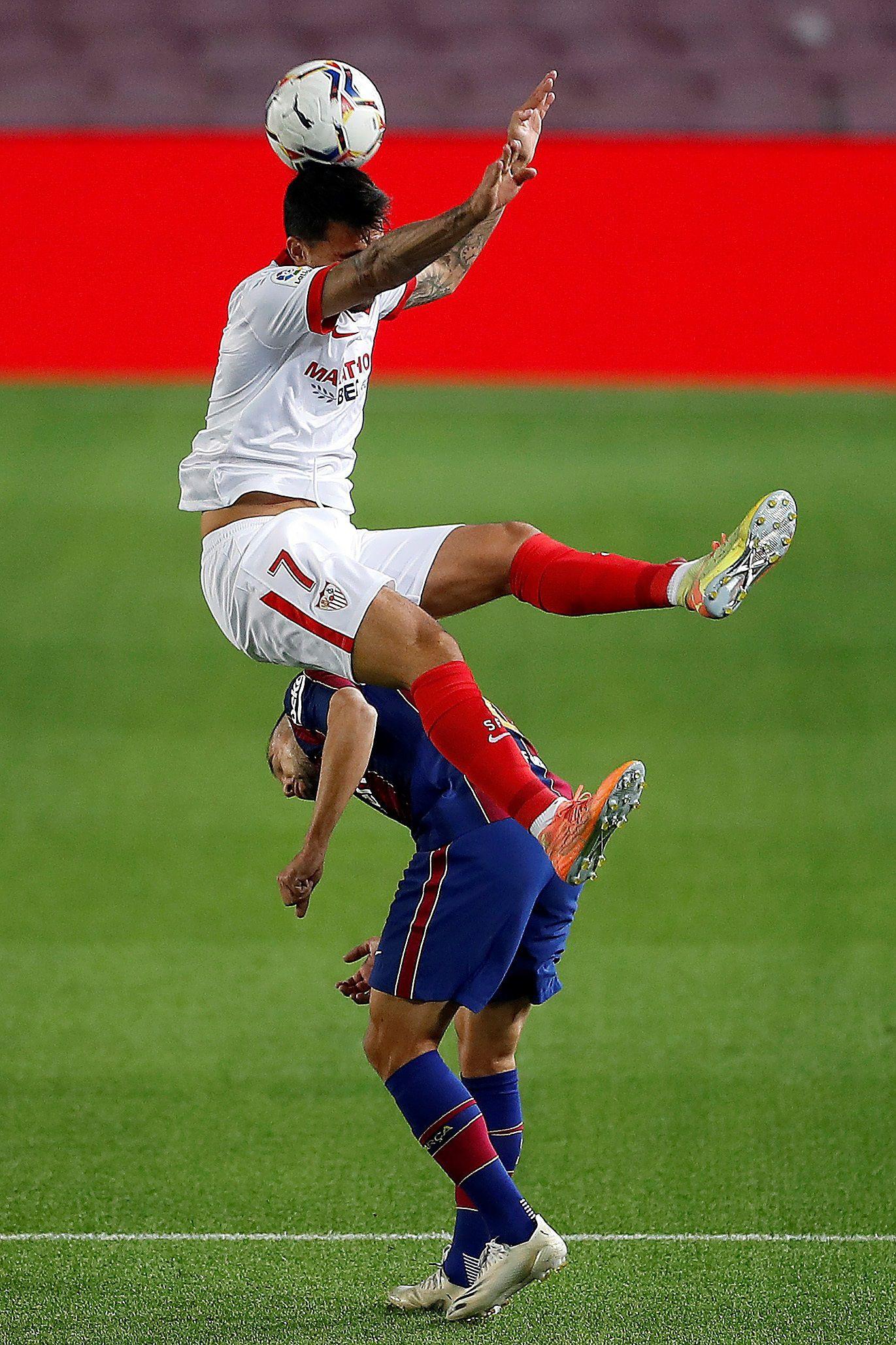 El defensa del FC Barcelona Jordi Alba (abajo) lucha con Suso Fernández, del Sevilla, en el partido de la quinta jornada de Liga en Primera División que FC Barcelona y Sevilla FC jugaron en el Camp Nou, en Barcelona. EFE/Alberto Estévez