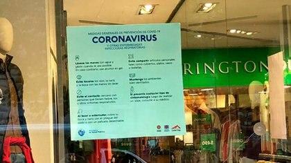 Las medidas de protección para los tiempos de coronavirus, en la vidriera de un comercio (Catalina Weiss)
