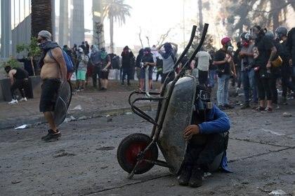 Un manifestante se refugia detrás de una carretilla durante una protesta contra el gobierno de Chile, en el primer aniversario de las protestas y disturbios que sacudieron la capital en 2019, en Santiago, Chile. REUTERS/Ivan Alvarado