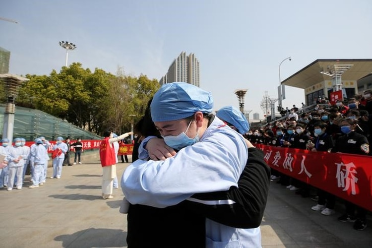 Un trabajador médico se despide de un compañero de trabajo en la estación de trenes de Wuhan, provincia china de Hubei (China Daily)
