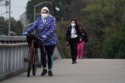 Personas usando tapabocas durante el aislamiento preventivo obligatorio decretado por el gobierno para frenar la expansión del coronavirus caminan sobre un puente peatonal en Bogotá, Colombia, 20 de marzo, 2020. REUTERS/Nathalia Angarita. NO VENTAS NO ARCHIVOS