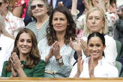 Kate, Duchess of Cambridge, left, and Meghan, Duchess of Sussex applaud as they sit in the Royal Box on Centre Court to watch the women's singles final match between Serena Williams of the United States and Romania's Simona Halep on day twelve of the Wimbledon Tennis Championships in London, Saturday, July 13, 2019. (AP Photo/Ben Curtis)