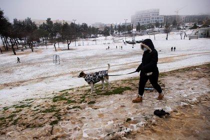 Una mujer camina con su perro en un parque en una mañana nevada en Jerusalén, 18 de febrero de 2021. REUTERS / Ronen Zvulun