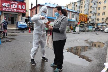 Un trabajador en traje de protección toma la medición de la temperatura corporal de una mujer después del brote de la enfermedad del coronavirus (COVID-19) en Jilin, provincia de Jilin, China, 17 de mayo de 2020. (cnsphoto vía REUTERS)