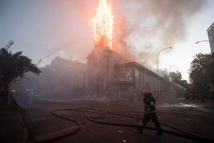 Un grupo de bomberos trabaja en la extinción del incendio de la parroquia de la Asunción este viernes en los alrededores de la Plaza Italia de Santiago (Chile), EFE/Alberto Valdés