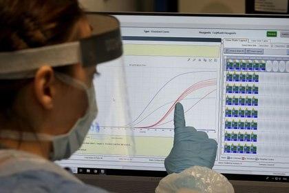 Un trabajadora de salud del nuevo laboratorio del Queen Elizabeth University Hospital en Glasgow explica la curva de contagios del coronavirus (REUTERS)