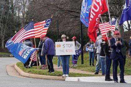 Los partidarios del presidente de los Estados Unidos, Donald Trump, ondean banderas antes de que su caravana salga del Trump National Golf Club en Sterling.  REUTERS/Joshua Roberts