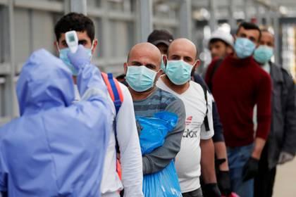 Trabajadores hacen fila para que les tomen la temperatura antes de ingresas a sus trabajos