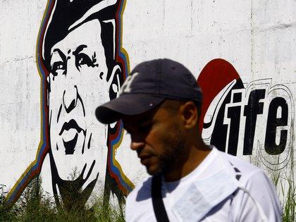 Un venezolano delante de una reproducción de Hugo Chávez