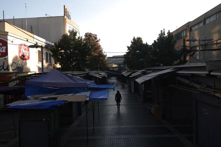 Una mujer camina en una calle rodeada de negocios cerrados en un sector comercial en Santiago durante una cuarentena preventiva tras el brote de la enfermedad de coronavirus (COVID-19), en Santiago de Chile (REUTERS/Pablo Sanhueza)