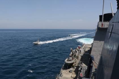 Cuatro embarcaciones de la Guardia Revolucionaria de Irán navegan cerca al USS Paul Hamilton, en abril (Reuters)