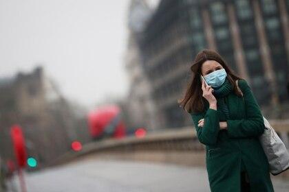 Una mujer camina por el puente Westminster prácticamente vacío en Londres (Reuters)