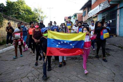 IMAGEN DE ARCHIVO. Migrantes venezolanos reaccionan cuando miembros de la Guardia Nacional (no en la fotografía) intentan detener su avance hacia la frontera con Colombia, en San Cristóbal, Venezuela. Octubre 12, 2020. REUTERS/Carlos Eduardo Ramirez