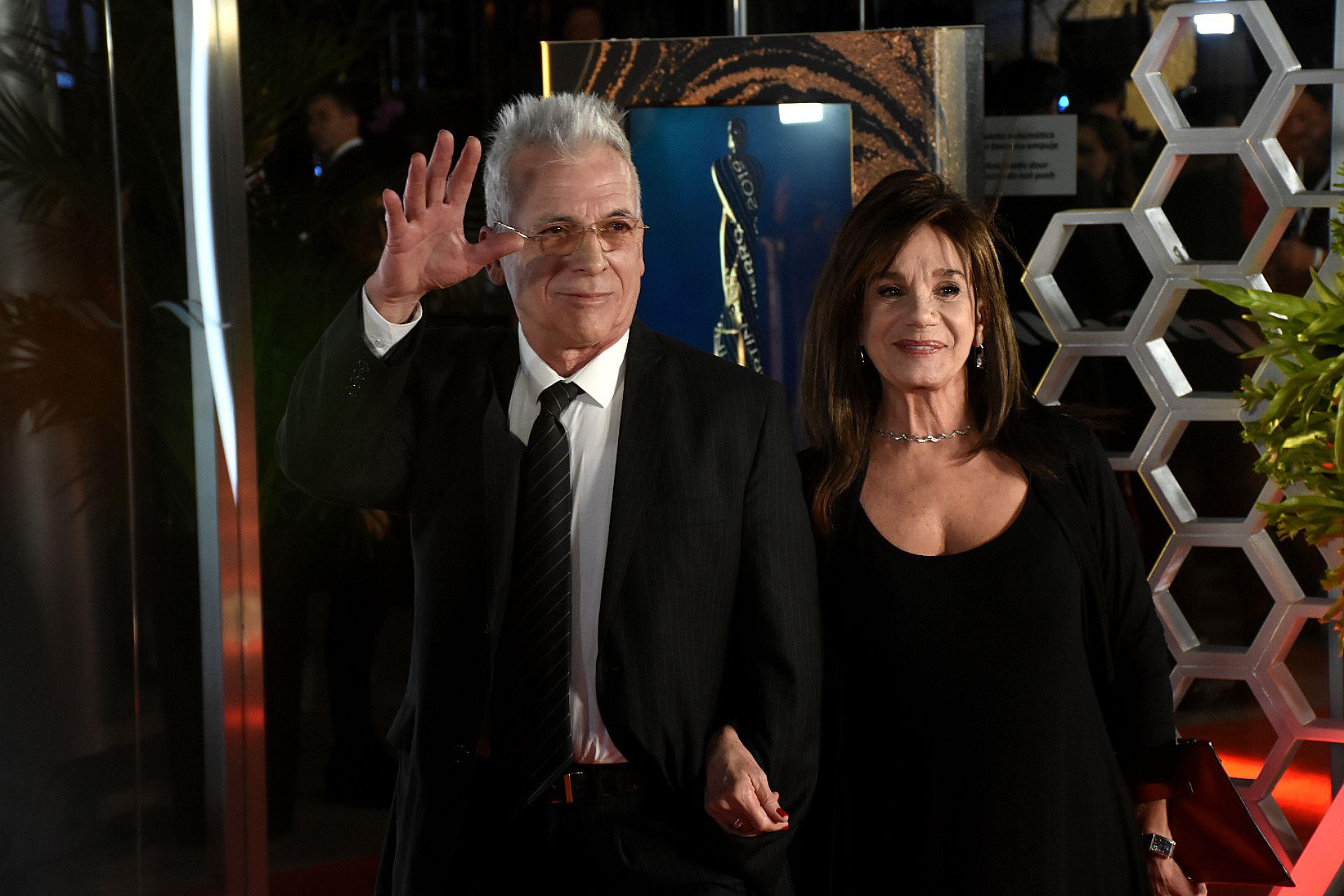 Gerardo Romano con un traje clásico en negro, camisa blanca y corbata rayada y Ana María Piccio con un total look black. Completó el look con mini pendientes y gargantilla de plata