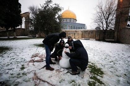 La gente arma un muñeco de nieve junto a la Cúpula de la Roca en el complejo conocido por los judíos como el Monte del Templo y por los musulmanes como el Noble Santuario durante una mañana nevada en la Ciudad Vieja de Jerusalén, el 18 de febrero de 2021. REUTERS / Ammar Awad