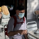 A man wearing a protective face mask sits at a table at an outdoor seating section of a Zurich bar at Catalunya square, as some Spanish provinces are allowed to ease lockdown restrictions during phase one, amid the coronavirus disease (COVID-19) outbreak, in Barcelona, Spain, May 25, 2020. REUTERS/Nacho Doce