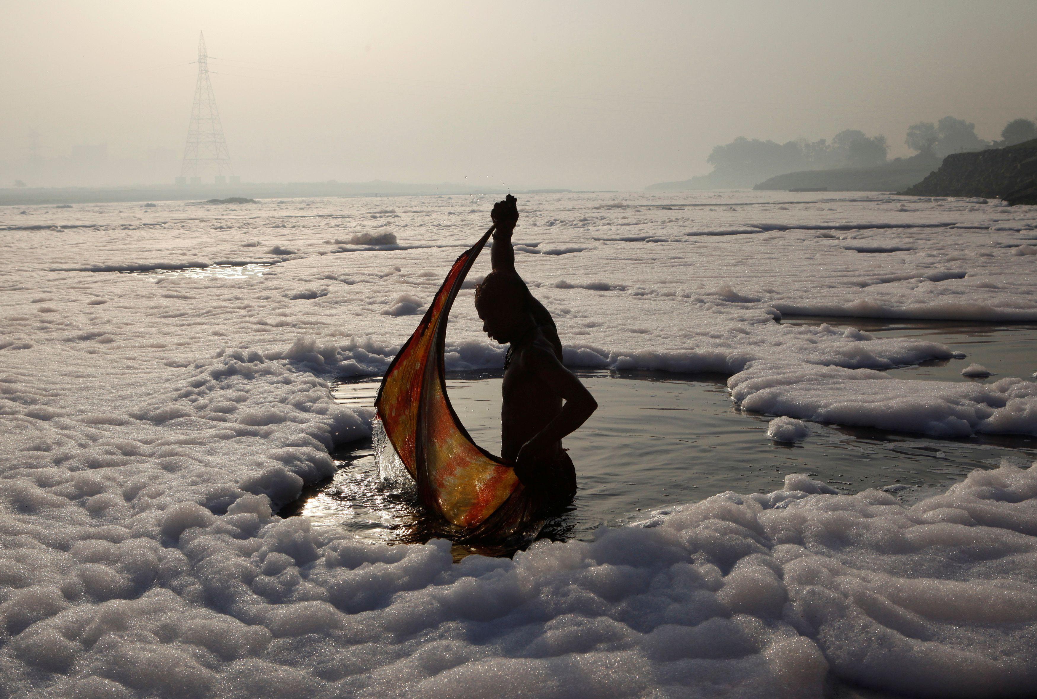 Un devoto hindú envuelve su tela después de un baño ritual en el contaminado río Yamuna en Nueva Delhi el 21 de marzo de 2010.