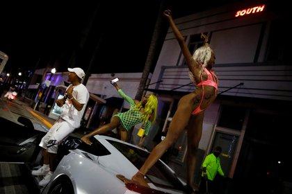 Una mujer baila sobre un auto durante una fiesta en Miami Beach (REUTERS/Marco Bello)