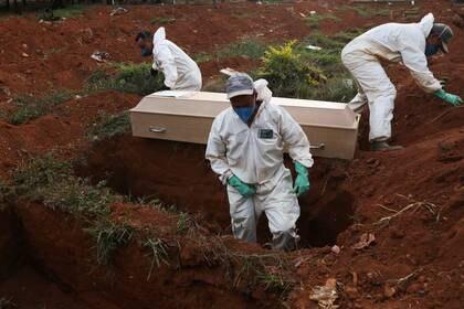 Sepultureros con trajes protectores preparan el entierro de una persona fallecida por coronavirus en el cementerio de Sao Paulo. Mayo 22, 2020. REUTERS/Amanda Perobelli