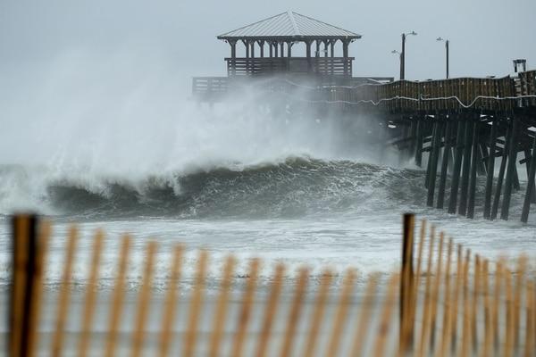 Las olas se estrellan debajo del muelle de Oceana Piers, en palya Atlanti, Carolína del Norte (AFP)
