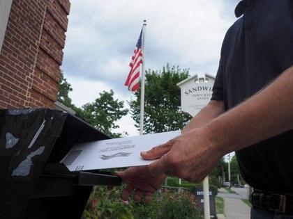 En las elecciones estadounidenses (Europa Press) una persona emite su voto por correo
