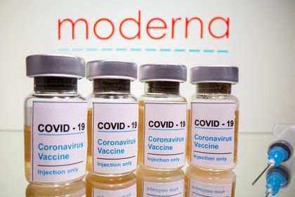 "FILE PHOTO: Vials with a sticker reading, ""COVID-19 / Coronavirus vaccine / Injection only"" and a medical syringe are seen in front of a displayed Moderna logo in this illustration taken October 31, 2020. REUTERS/Dado Ruvic/Illustration/File Photo"