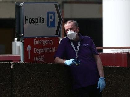 Un hombre descansa en las afueras del hospital St. Thomas, donde está internado el premier Boris Johnson (Reuters)