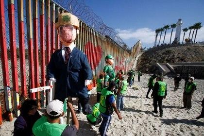 Migrantes y miembros de la sociedad civil sostienen piñatas estilo Trump para protestar contra las solicitudes de asilo bloqueadas y la construcción del muro (Foto: REUTERS / Jorge Duenes)