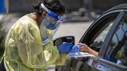 03/06/2020 03 June 2020, US, Los Angeles: A medical worker wears protective equipment takes a sample from a person at a drive-through COVID-19 testing clinic at the Weingart YMCA Wellness and Aquatic Center. Photo: Hans Gutknecht/Orange County Register via ZUMA/dpa POLITICA INTERNACIONAL Hans Gutknecht/Orange County Reg / DPA
