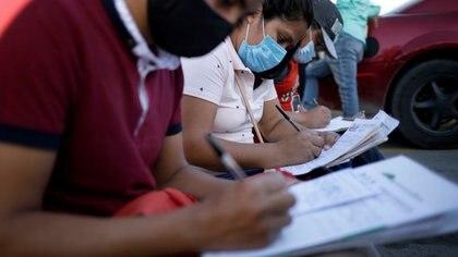 Los solicitantes de empleo completan formularios de solicitud de empleo para fábricas de ensamblaje mientras continúa el brote de la enfermedad del coronavirus (COVID-19) en Ciudad Juárez, México, el 17 de junio de 2020. Fotografía tomada el 17 de junio de 2020. REUTERS / José Luis González/ Foto de archivo