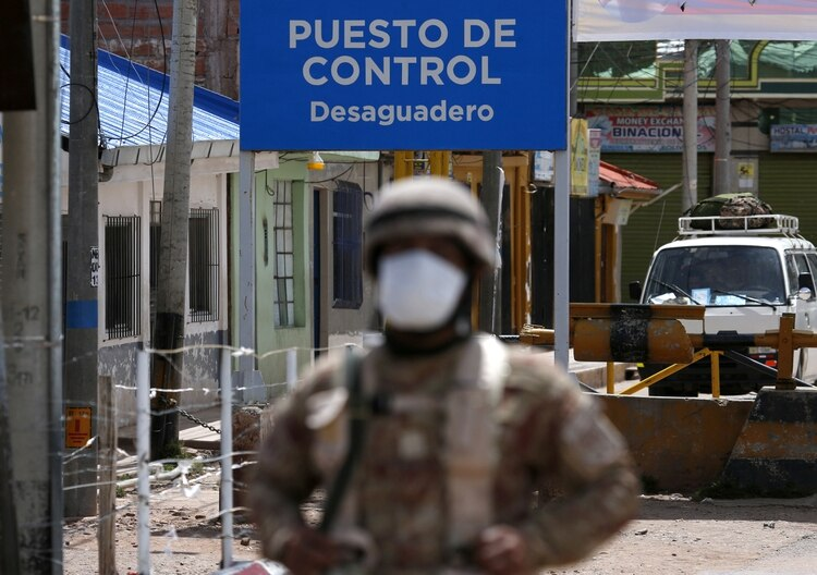 A Peruvian soldier stands at the check point in border line between Peru and Bolivia after Peru's government's announcement of the border closure in a bid to slow the spread of the new coronavirus (COVID-19), in Desaguadero, Bolivia, March 17, 2020. REUTERS/David Mercado