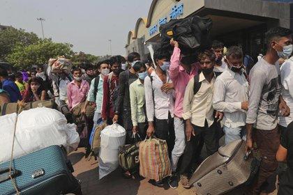 Las personas que usan máscaras como precaución contra el coronavirus hacen cola para abordar los trenes en la terminal Lokmanya Tilak Terminus en Mumbai