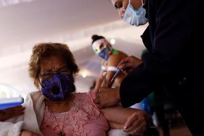 Imagen de archivo. Una mujer reacciona después de recibir una vacuna contra el COVID-19 durante un programa de vacunación masiva, mientras luchadores de lucha libre alientan a los ancianos a vacunarse, en la Ciudad de México, México. 2 de abril de 2021. REUTERS / Carlos Jasso