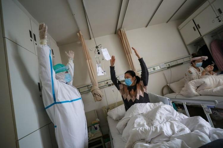 FOTO DE ARCHIVO. Un trabajador del equipo médico con traje protector muestra a una paciente los ejercicios de rehabilitación en una sala del Hospital de la Cruz Roja en Wuhan, China, el epicentro del nuevo brote de coronavirus. 24 de febrero de 2020. Imagen obtenida por un tercero. China Daily vía REUTERS.