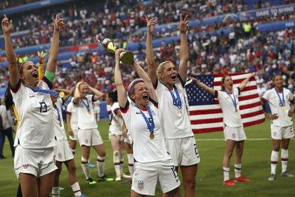 Megan Rapinoe (centro) con el trofeo de campeonas de la Copa Mundial femenina tras la victoria de Estados Unidos por 2-0 ante Holanda en la final en Lyon, Francia, el domingo 7 de julio de 2019. (AP Foto/Francisco Seco)