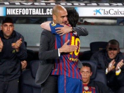 Foto de archivo del delantero de Barcelona Lionel Messi abrazando a Pep Guardiola tras marcar ante Espanyol por la liga española en el Nou Camp.  May 5, 2012.     REUTERS/Gustau Nacarino