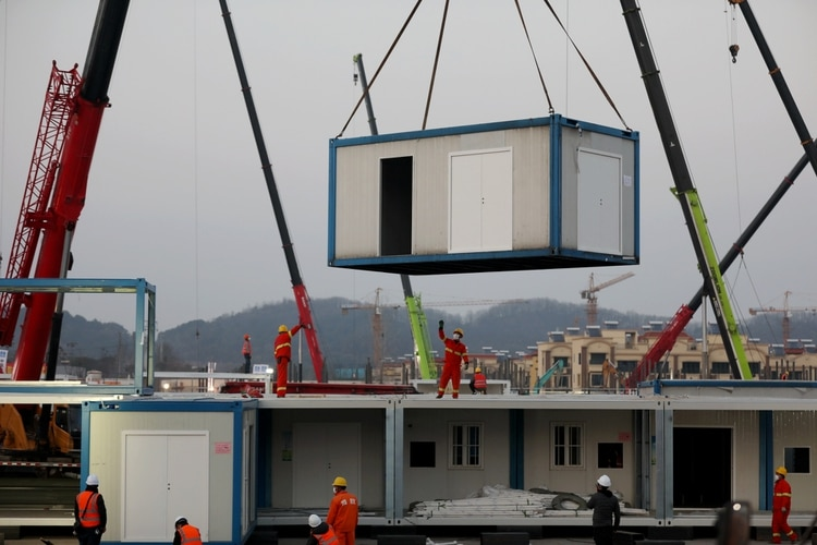 Trabajadores en la obra de construcción del nuevo Hospital Huoshenshan, un hospital improvisado para el tratamiento de pacientes del nuevo coronavirus, en Wuhan, provincia de Hubei (China), el 30 de enero de 2020 (China Daily via REUTERS)