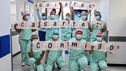 Las enfermeras de la Clínica Versalles de Cali sosteniendo los carteles con los que Jefferson Riascos le pidió matrimonio a Diana Paola Angola (Photo by Luis ROBAYO / AFP)