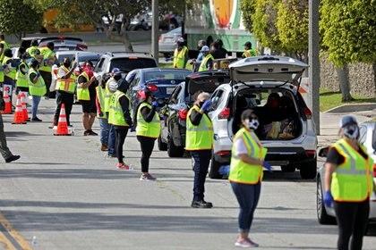 Decenas de voluntarios realizan controles en los automóviles que se desplazan hacia Los Angeles en medio de las restricciones por la pandemia -  REUTERS/Patrick T. Fallon