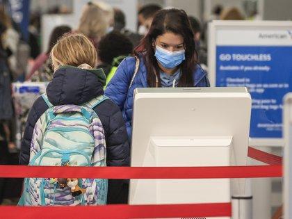 Personas se alistan para viajar en el Aeropuerto Internacional O'Hare en Chicago, Illinois, este 25 de noviembre de 2020 (EFE/ Tannen Maury)