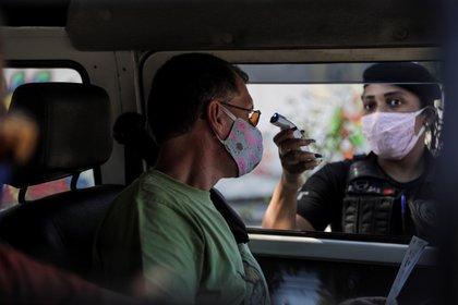 Un agente de seguridad del ayuntamiento de la ciudad de Niterói toma la temperatura de un hombre en Niterói, Río de Janeiro (EFE)