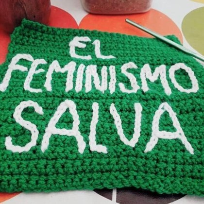 Un cuadradito tejido para formar parte de la bandera femenista