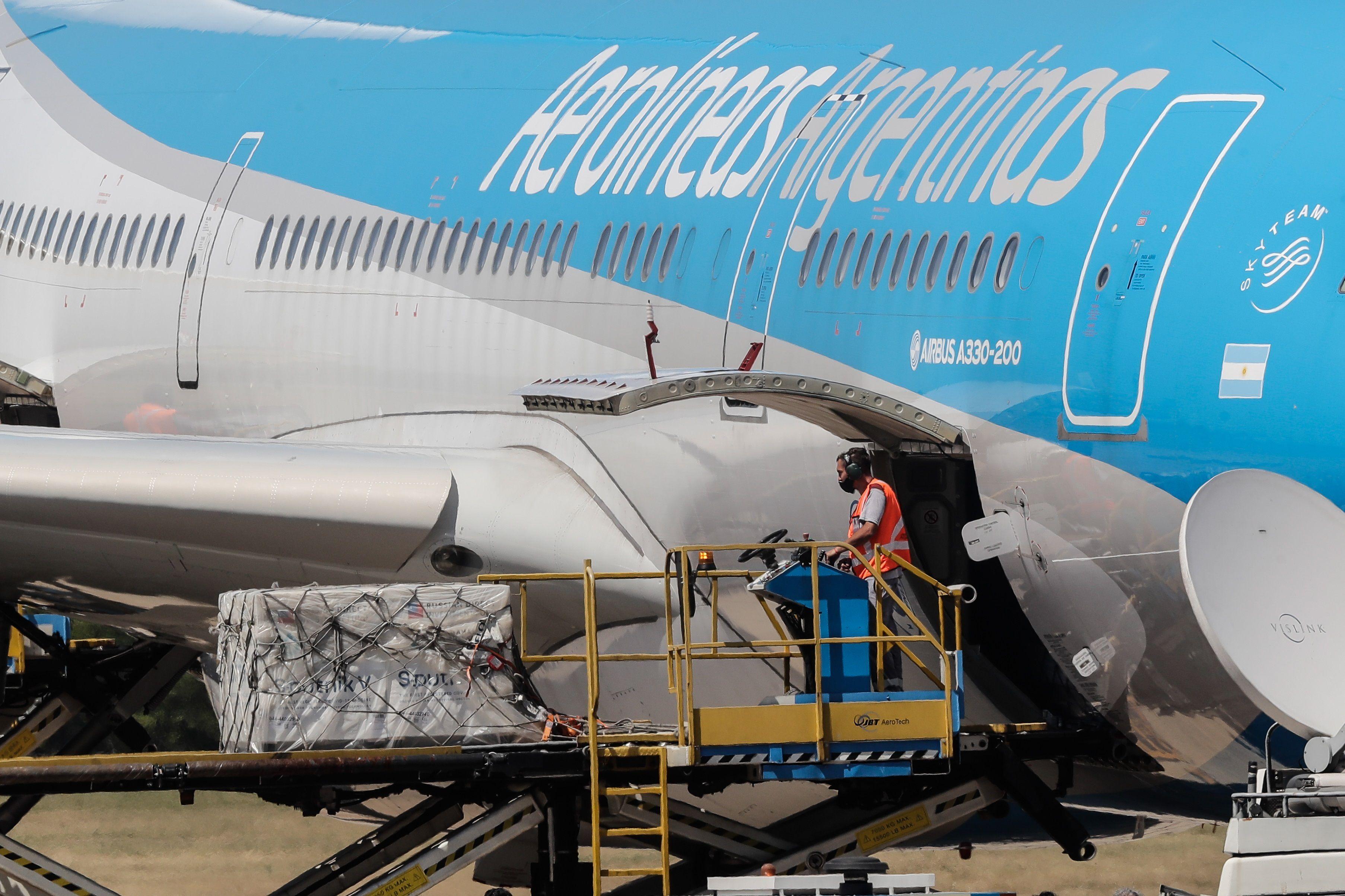Operarios descargan de un avión de Aerolíneas Argentinas los primeros contenedores de la vacuna rusa Sputnik-V contra la covid-19, el 24 de diciembre de 2020, en el Aeropuerto de Ezeiza en Buenos Aires (Argentina). EFE/Juan Ignacio Roncoroni/Archivo