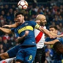 Pablo Perez of Argentina's Boca Juniors, 8, heads the ball pressures by Javier Pinola of Argentina's River Plate, back, during the Copa Libertadores final soccer match at the Santiago Bernabeu stadium in Madrid, Spain, Sunday, Dec. 9, 2018. (AP Photo/Andrea Comas)