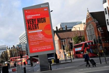 Los peatones pasan por delante de un anuncio de información sanitaria del gobierno británico que destaca las nuevas restricciones en medio de la propagación de la enfermedad coronavirus (COVID-19), Londres, Gran Bretaña, 19 de diciembre de 2020. REUTERS/Toby Melville