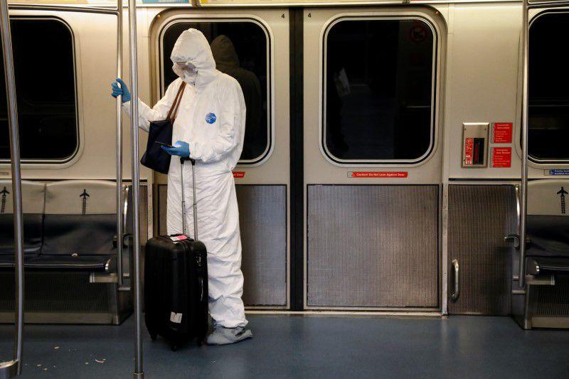 Una mujer con el equipo de protección personal (EPP) viaja en un tren aéreo en el Aeropuerto Internacional John F. Kennedy de la ciudad de Nueva York, EEUU, el 20 de marzo de 2020. REUTERS/Brendan McDermid