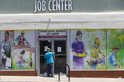 Un trabajador mira hacia el interior del Centro de Empleo Comunitario de Pasadena, en California, el jueves 7 de mayo de 2020, durante el brote de coronavirus. (AP Foto/Damian Dovarganes)