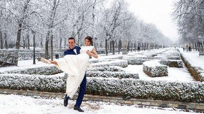 MADRID 07/01/2021.- Los recién casados Julio y Yone posan en el parque del Retiro durante una nevada este jueves en Madrid. EFE/Emilio Naranjo