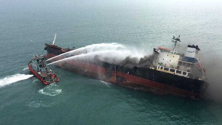 Los equipos antiincendio y de rescate seguían trabajando con el buque petrolero (AFP)
